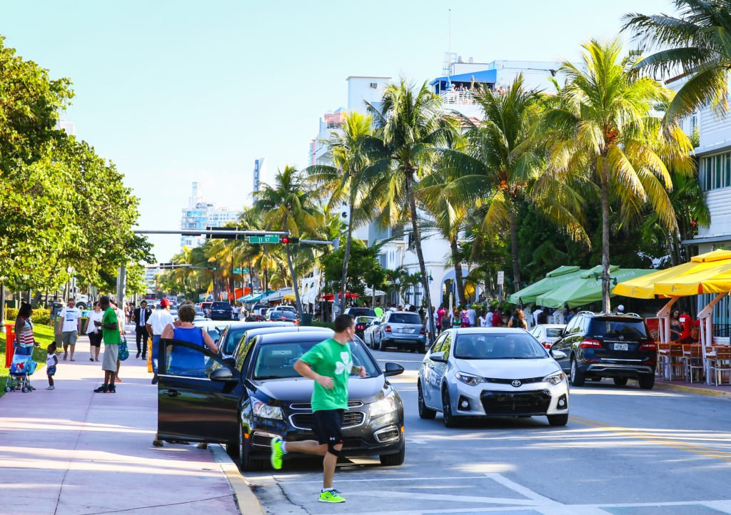 MIAMI BEACH, USA - MAY 9, 2015: Cars driving and parking, people walking by or running, street cafes with sunshades on the side of the Ocean Drive.; Shutterstock ID 395708740