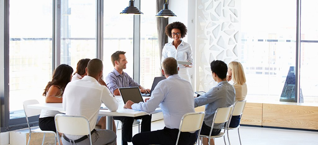 team members listen to businesswoman giving meeting